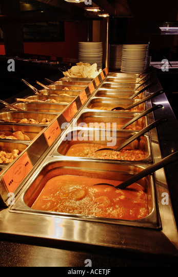 Serving trays of curry at an Indian Restaurant, UK - Stock Image