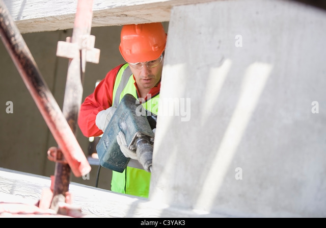 Building worker handling a drill - Stock Image