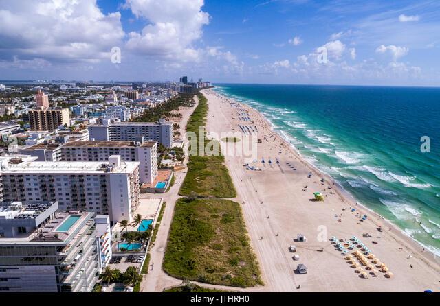 Miami Beach Florida aerial overhead view above bird's eye view Atlantic Ocean sand sunbathers residential condominium - Stock Image