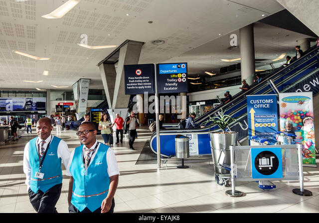 South Africa African Cape Town International Airport CPT terminal Black man coworkers employees uniform inside interior - Stock Image