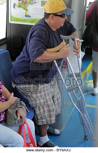 Miami Beach Florida Metrobus South Beach Local bus transportation crutches man disabled rider passenger gets up - Stock Image