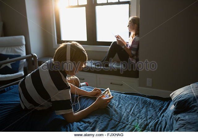 Brother and sister using digital tablets in bedroom - Stock Image