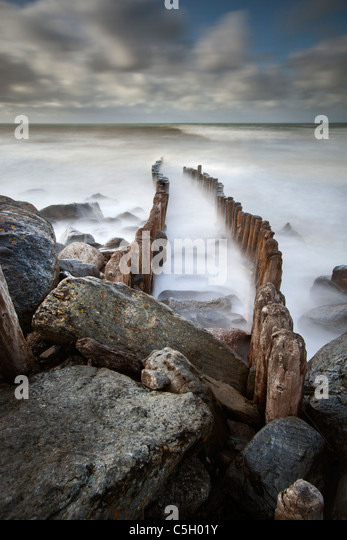 Wooden stumps and rocks forming the sea defenses at Lynton on the North Devon coast, England, United Kingdom - Stock Image