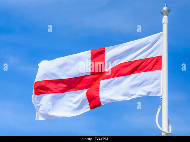 St Georges Cross flag, the flag of England, flying against blue sky. - Stock Image