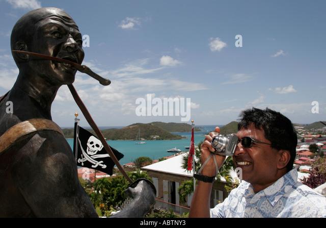 St. Thomas USVI Charlotte Amalie Blackbeard's Hill pirate statue Jolly Roger pirate flag Asian male camera - Stock Image