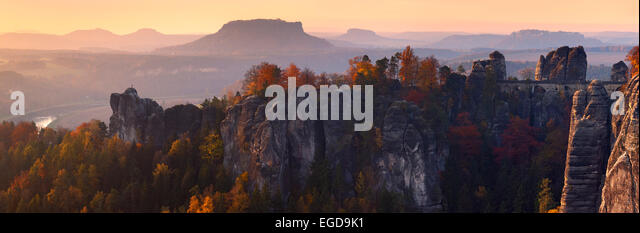 The first sunlight reaches the Bastei Bridge and the mountain tops of the Elbe Sandstone Massif in Autumn, Saxon - Stock Image