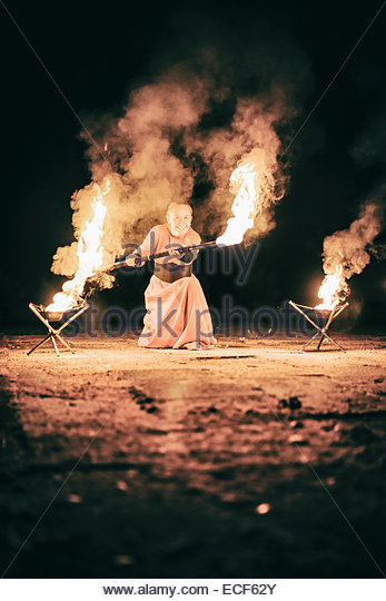 active the European girl in original suit carries out tricks for fire show at night - Stock Image
