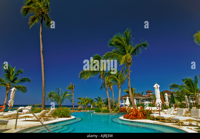 Four Seasons Resort swimming pool, palm trees, blue sky background, island of nevis, leeward islands - Stock Image