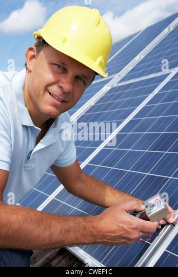 Man installing solar panels - Stock Image