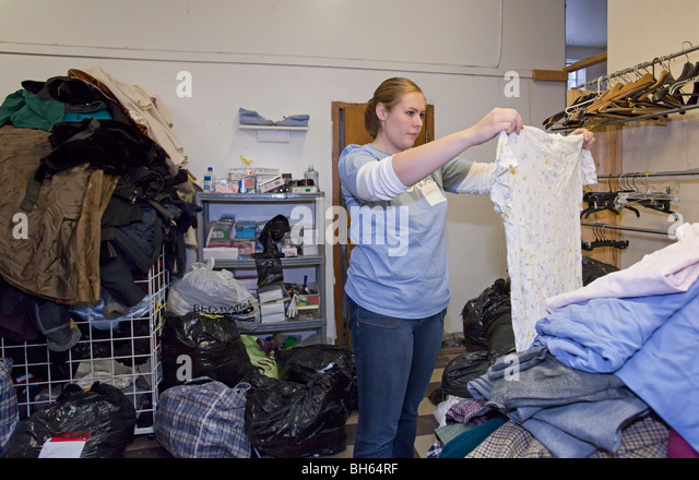 Volunteer Sorts Donated Clothing at Thrift Shop - Stock Image