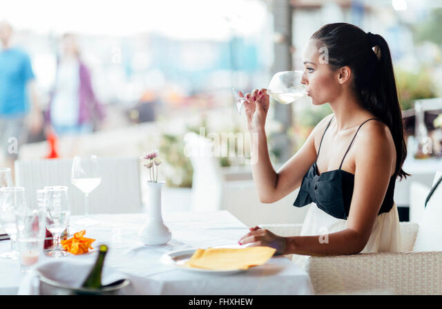 Woman tasting white wine in restaurant and lifting glass accordingly - Stock-Bilder