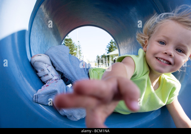 Close-up of girl reaching for camera, lying in playground tunnel - Stock Image