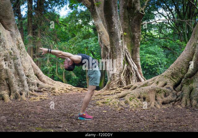 Young man practicing yoga in park, Sao Paulo, Brazil - Stock Image