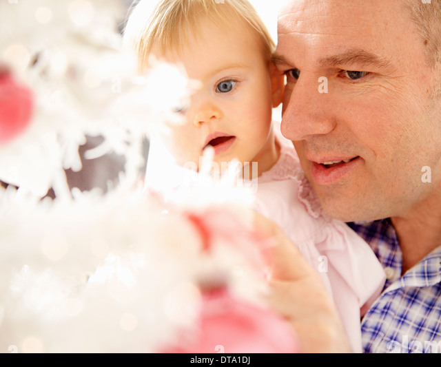 Father and Baby Daughter Looking at Christmas Tree, Close-up view - Stock Image