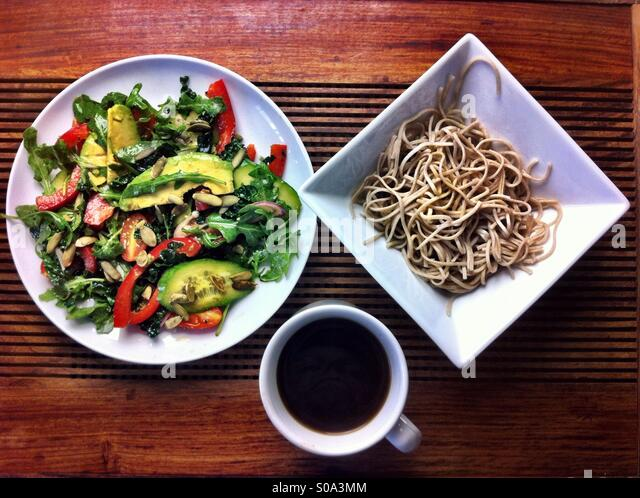 Vegan lunch - soba noodles in square bowl, salad on round white plate and coffee  in white mug served on a dark - Stock Image