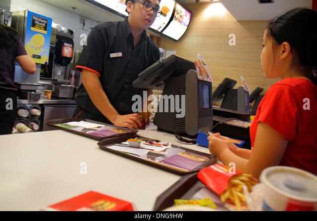 Hong Kong China Kowloon Sham Shui Po McDonald's fast food restaurant counter employee job Asian man girl customer - Stock Image