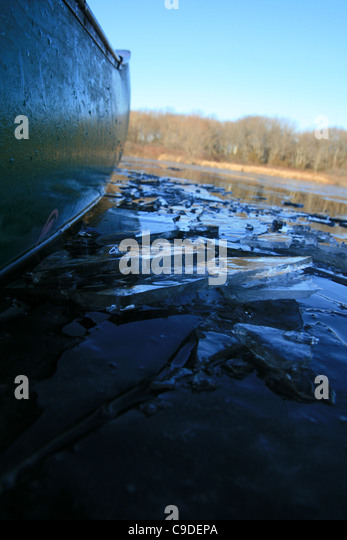detail of the side of a green canoe breaking through icy water - Stock Image