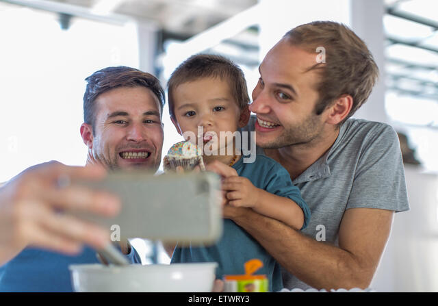 Gay couple baking cake with son - Stock Image