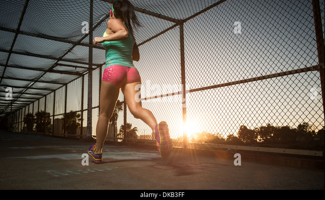 Female athlete running along walkway - Stock Image