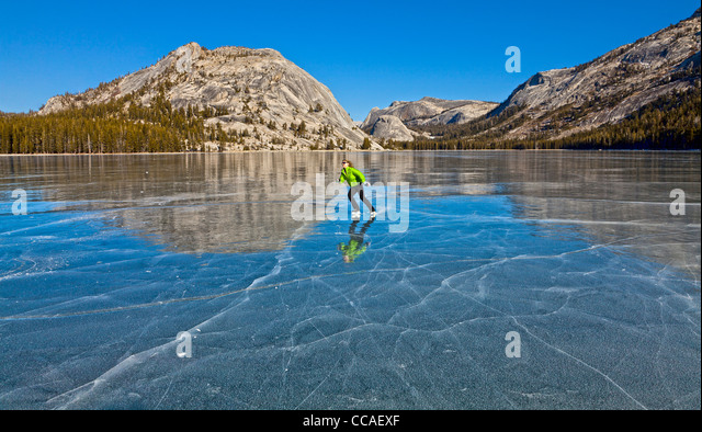 Ice skating on frozen Tenaya Lake in Yosemite National Park. - Stock Image