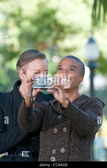 two middle aged woman have fun in the park taking photos - Stock Image