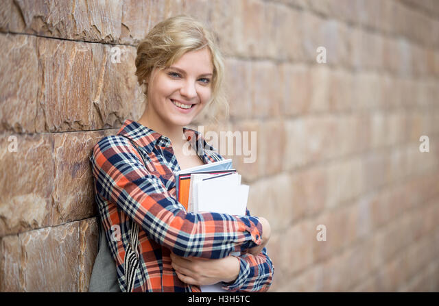 Portrait of a student with a books against the brick wall - Stock Image