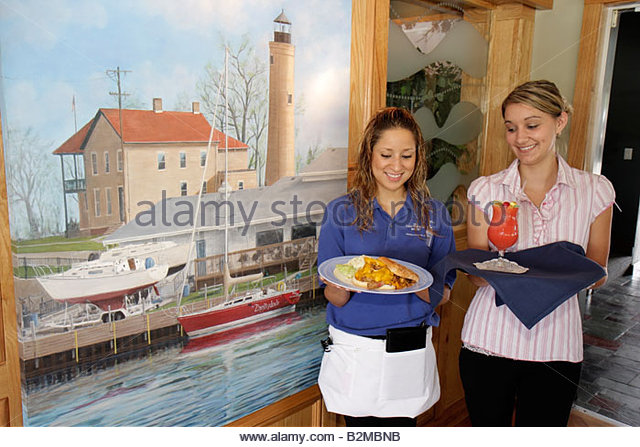 Wisconsin Kenosha Simmons Island Bluefish Restaurant Kenosha Yacht Club lighthouse mural Hispanic girl teen waitress - Stock Image