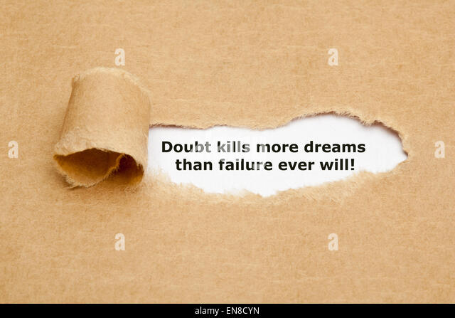 The text Doubt kills more dreams than failure ever will, appearing behind torn brown paper. - Stock Image