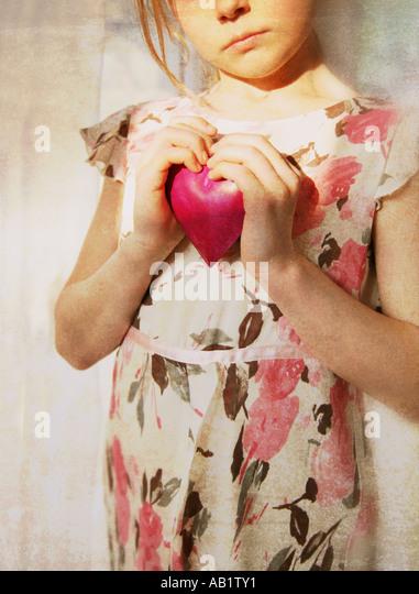 a girl holding a pink heart - Stock-Bilder