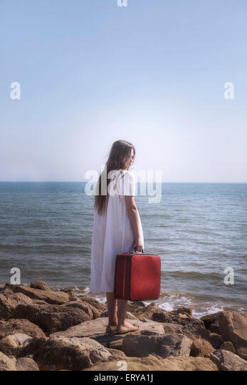 a girl with a red suitcase standing at the sea - Stock Image
