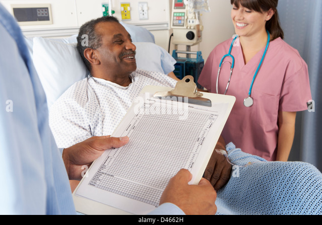 Doctor Looking At Chart With Senior Male Patient - Stock Image