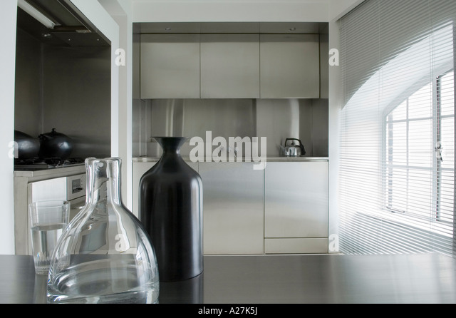 Stainless steel kitchen with glass vase detail in minimalist warehouse conversion - Stock Image