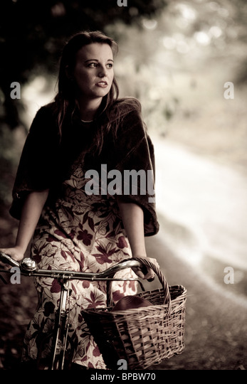 Girl with a bicycle in a vintage 1940 style - Stock Image