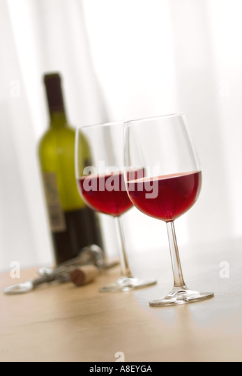 TWO RED WINE GLASSES AND BOTTLE ON TABLE TOP IN FRONT OF LIGHT WINDOW - Stock Image