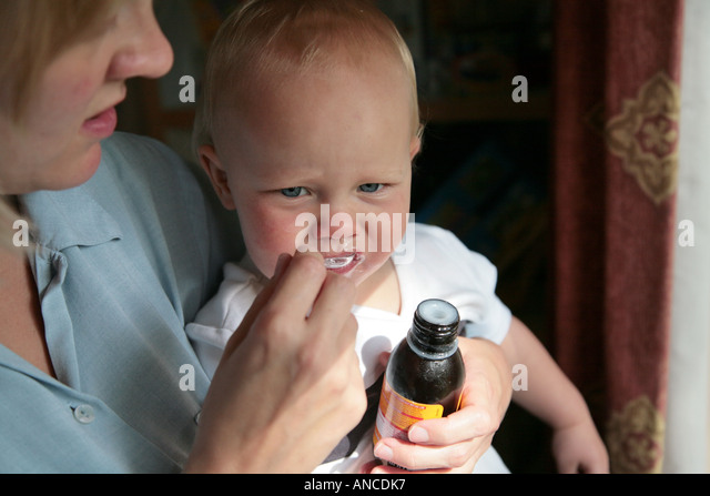 baby being given spoonful of medicine - Stock-Bilder