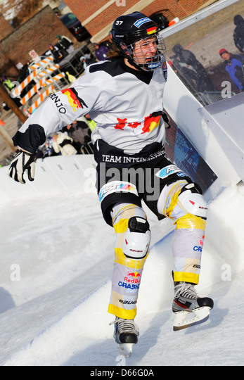 A competitor in the Red Bull Crashed Ice competition skates down the track during competition at the St. Paul Winter - Stock Image