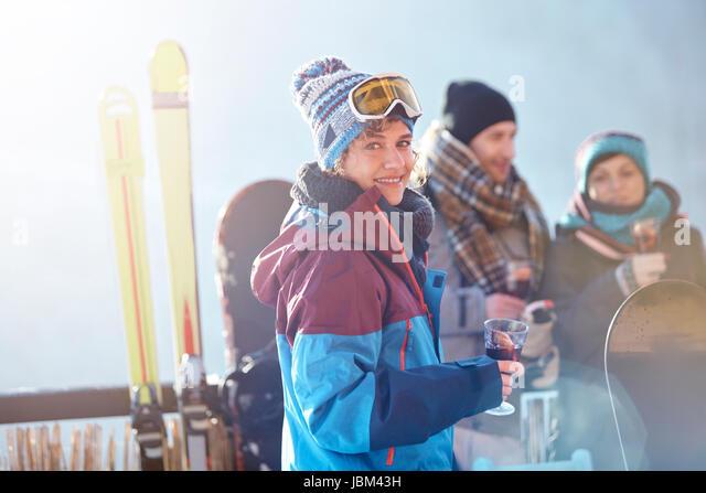 Portrait smiling female skier drinking cocktail on balcony with friends apres-ski - Stock-Bilder