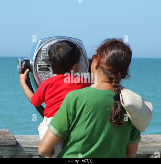 Clearwater Beach.Pier 60 Asian woman and child  look out to sea.Long range binocular machine. - Stock-Bilder