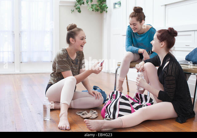 Three teenage girls chatting and laughing in ballet school - Stock Image
