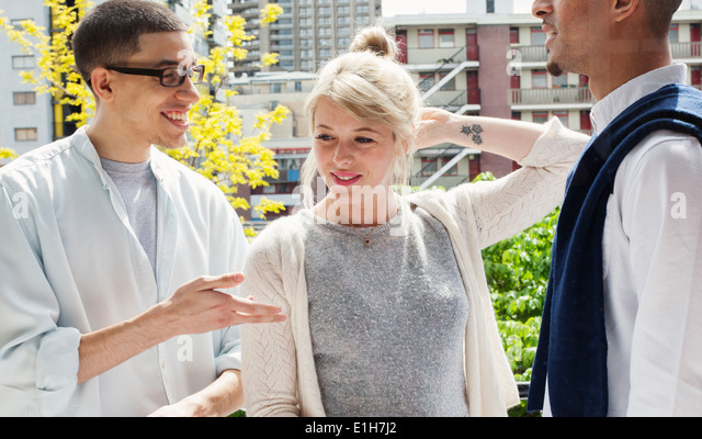 Young adults standing on balcony in London, UK - Stock Image