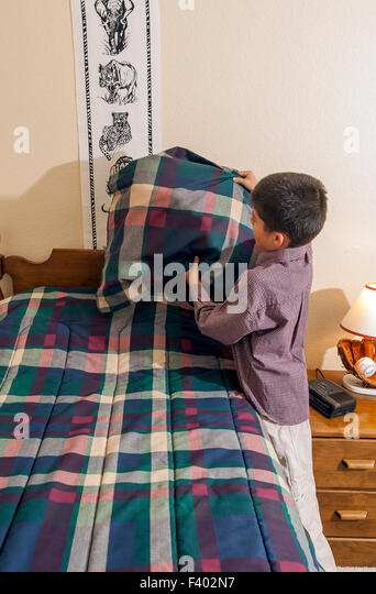 Boy Child children making bed tidy tidying bedroom multi inter racial diversity racially diverse multicultural cultural - Stock-Bilder
