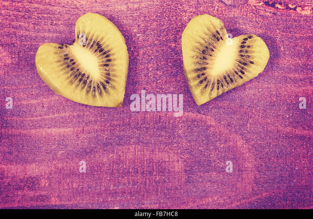 Vintage toned hearts made of kiwi on wooden background, space for text. - Stock Image