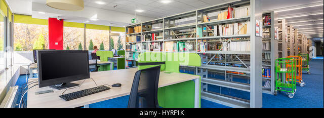 Panorama of functional library interior with wooden desks, office chairs, computers and bookshelves - Stock Image