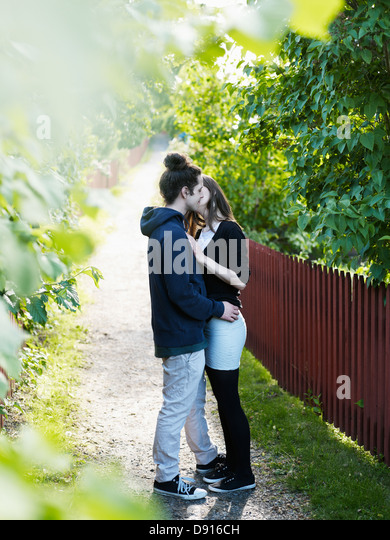 Young couple kissing outdoors - Stock-Bilder