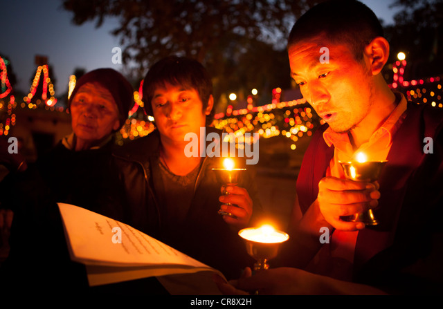 Buddhist monks and pilgrims pray with oil lamp at night , Mahabodhi Temple, Bodh Gaya, Bihar, India - Stock-Bilder