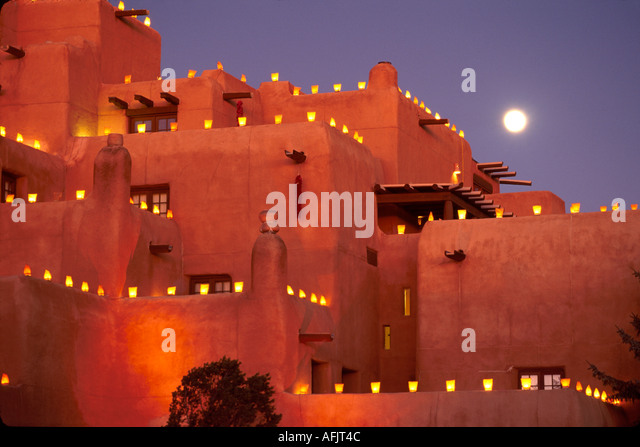 New Mexico Southwest Santa Fe Loretto Hotel Pueblo style architecture outlined by Christmas firolitos dusk moon - Stock Image