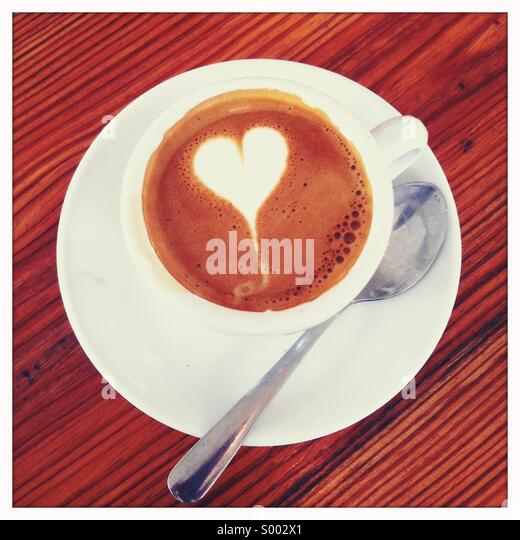 Looking down on a coffee drink in cup with a spoon and a decorated garnish - Stock-Bilder