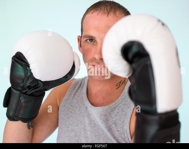 Man wearing boxing gloves about to fight - Stock Image
