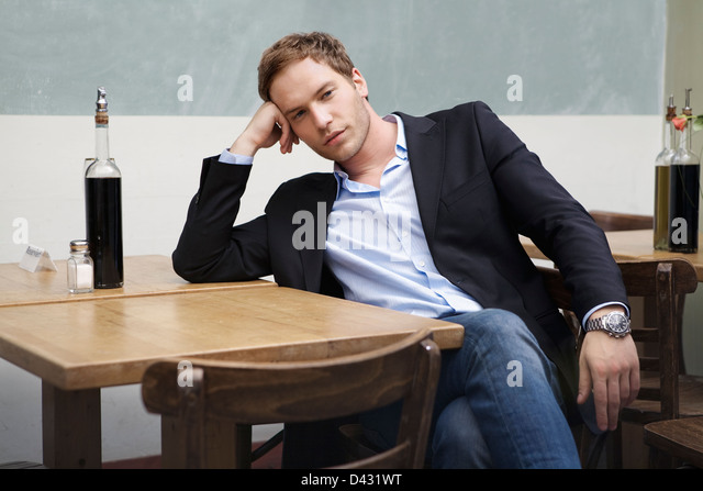 a man waiting for his date on a table reserved for two. - Stock Image