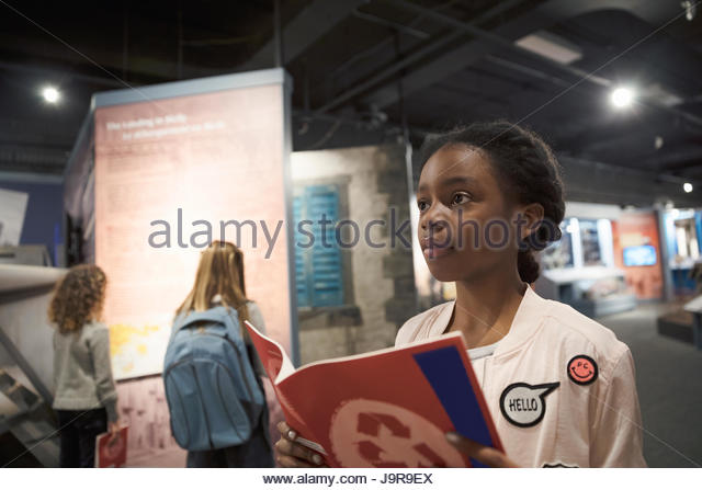 Curious African American girl student with notebook on field trip in war museum - Stock-Bilder